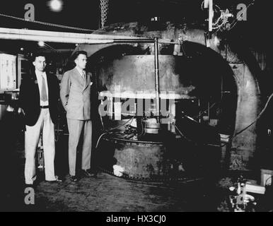 Scientists Ernest O, 1934. Lawrence and M. Stanley Livingston standing in front of the Cyclotron, a particle accelerator - Stock Photo
