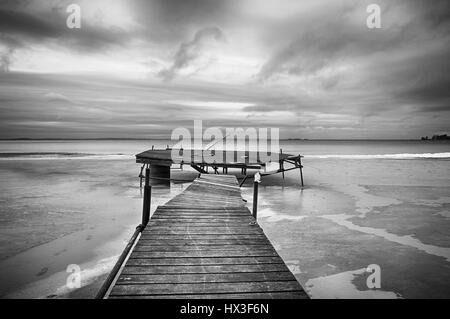 Black and white image of jetty on a beach in winter. - Stock Photo