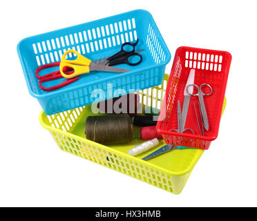 Colorful plastic baskets for domestic use, little household items in small boxes containers, spools of thread, scissors, - Stock Photo