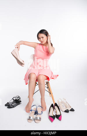 Pretty young asian woman having difficult choice to try on a few pairs of high heels - Stock Photo
