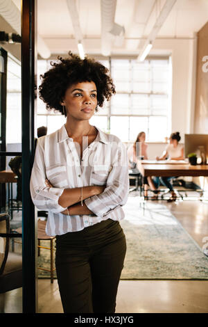 Portrait of young african woman leaning to office doorway and looking away. Thoughtful female executive at office - Stock Photo