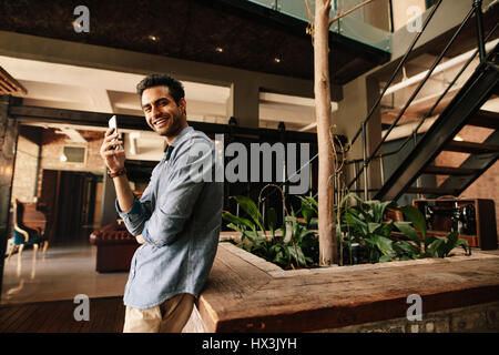 Portrait of handsome young man standing in modern office with mobile phone looking at camera and smiling. Business - Stock Photo