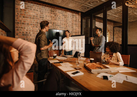 Shot of a group of young business professionals having a meeting in boardroom. Office workers discussing new business - Stock Photo