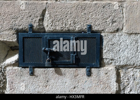 Closed metal door with a padlock on a stone wall - Stock Photo