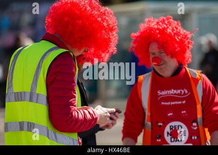 Blackpool, Lancashire, UK.  24th March 2017.  Red Nose Day as Sainsbury sponsored male fundraisers in red wigs, - Stock Photo