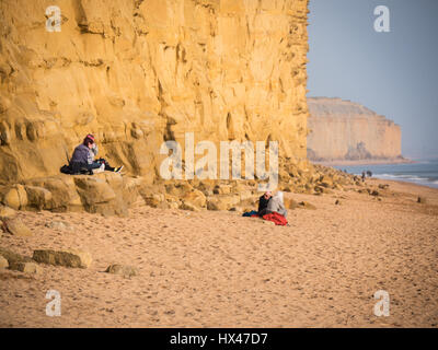 West Bay, Dorset, UK. 24th March 2017. People enjoying the sun below the East Cliff as the cloud finally clears - Stock Photo