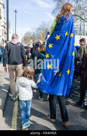 London, UK. 25th Mar, 2017. Tall looking young girl being carried on her dad's shoulders with EU flag on her back. - Stock Photo