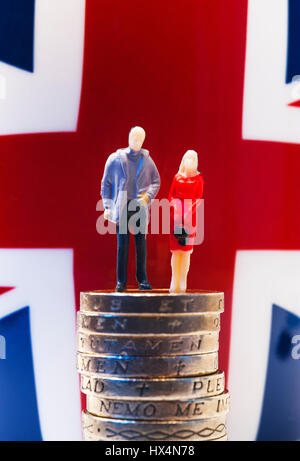 Miniature figures of man and woman standing on sterling coins with Union flag in background - Stock Photo