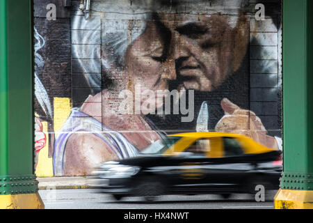 a taxi porteo in foreground and a giant wall art showing a couple of tango dancers