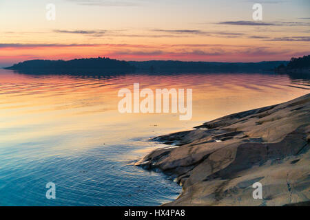 THE SWEDISH FINNISH ARCHIPELAGO IN THE BALTIC SEA AT SUNSET OR SUNRISE WITH RICH COLOURS AND ROCKS IN THE FOREGROUND - Stock Photo