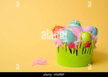 a pile of different decorated easter eggs in a basket decorated as grass and some pink feathers against a yellow - Stock Photo