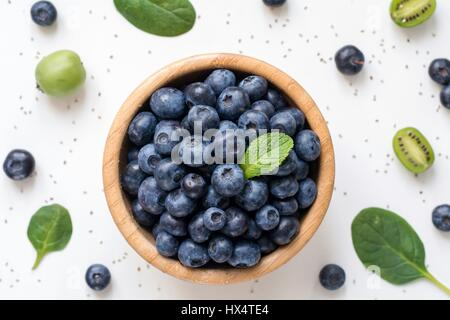 Blueberries in wooden bowl, top view. Flat lay or food pattern with blueberries, baby spinach, baby kiwi and chia - Stock Photo