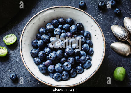 Top view of fresh blueberries in white ceramic bowl on dark stone table. Closeup - Stock Photo