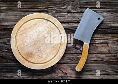 Old meat cleaver or butcher knife and round wooden chopping board. Top view with copy space - Stock Photo