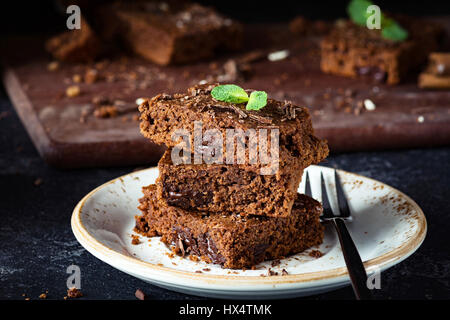 Brownies with chocolate decorated with mint leaf on a dessert plate, closeup view - Stock Photo