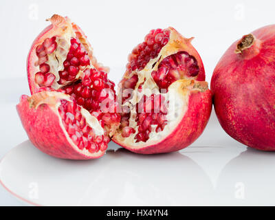 The Ripe pomegranate fruit and broken into four parts, on a wite porcelain plate. The whole garnet fruit is to the - Stock Photo