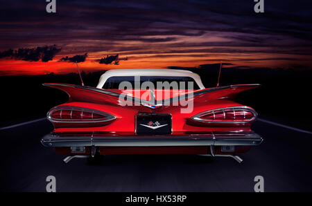 Red 1959 Chevrolet Impala Convertible classic retro car rear view on a highway in colorful red twilight nighttime - Stock Photo