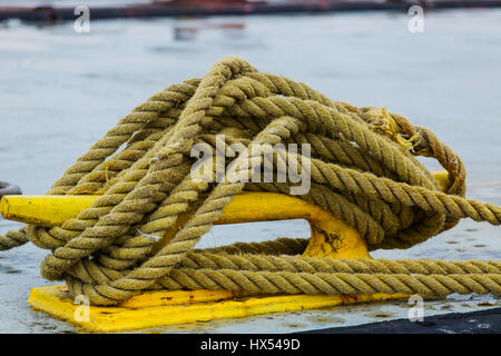 Cleat with ropes used to tie up a boat at the dock.