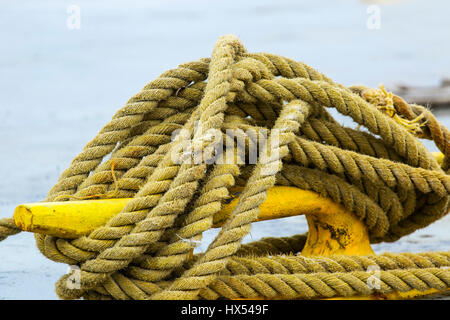 Cleat with ropes used to tie up a boat at the dock. - Stock Photo
