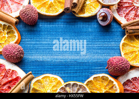 Lychee fruits with citrus slices and star spices on wooden background - Stock Photo
