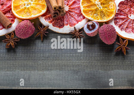 Lychee fruits with citrus slices and star spices on wooden background Stock Photo