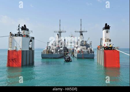 In calm turquoise waters two mine countermeasure ships USS Pioneer and USS Warrior prepare for transport behind - Stock Photo