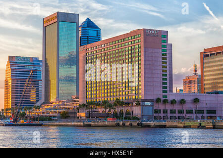 Sunset on downtown buildings and bridges on St Johns River in downtown Jacksonville, Florida. - Stock Photo