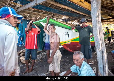 Traditional fishermen having a conversation at dry boat storage in Lamalera village, Lembata Island, East Nusa Tenggara, - Stock Photo