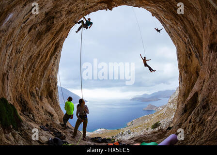 Rock climbers in cave: belayers watching leading climbers, two climbers swinging on ropes or being lowered down, - Stock Photo