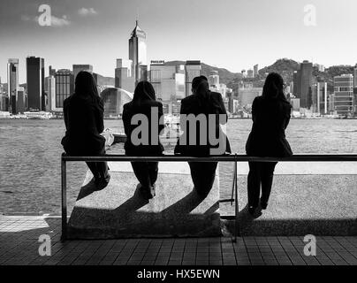 Four office workers take a lunch break overlooking Hong Kong's Victoria Harbour - Stock Photo