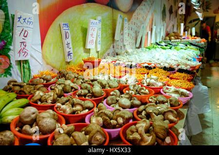 Mushrooms and vegetables on sale at a greengrocer's in Shau Kei Wan market. Hong Kong Island, Hong Kong, China. - Stock Photo