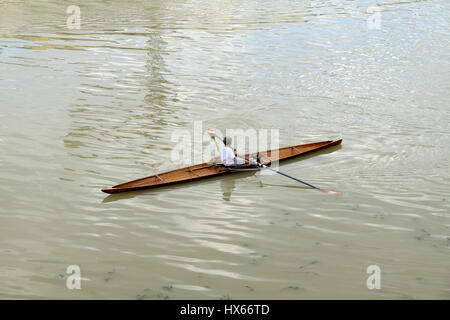 Young boy rowing on the river on a classic wooden racing boat - Arno river waterway by Ponte alle Grazie bridge, - Stock Photo