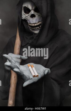 The concept: smoking kills. Grim reaper holding cigarette. Studio shot over black background - Stock Photo