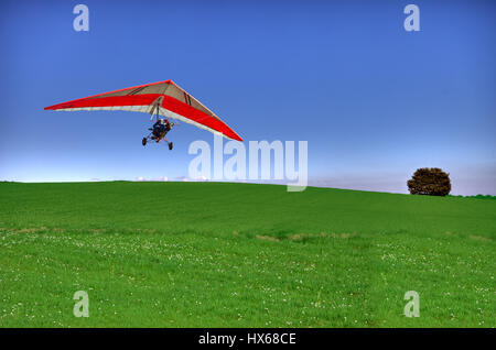 A hang glider flying over a country scene, in a very clear, sunny day - Stock Photo