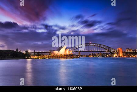Sydney, Australia - 19 March 2017: World famous Australian landmarks Sydney Opera house and Harbour bridge across - Stock Photo