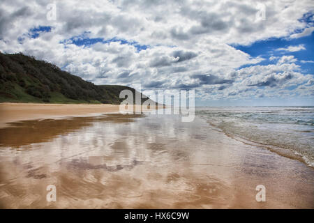 Fraser island 75 miles beach facing pacific ocean on cloudy summer day. Green hills and surfing waves coming on - Stock Photo