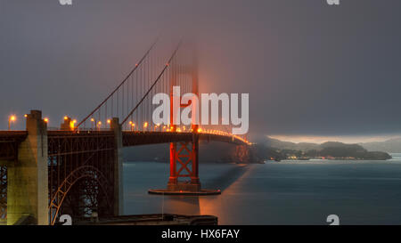 Magic hour at the Golden Gate Bridge at sunset in fog. - Stock Photo