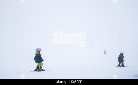 Two small children, having a skiing lesson, in very foggy conditions, in Meribel, France, in the French Alps - Stock Photo
