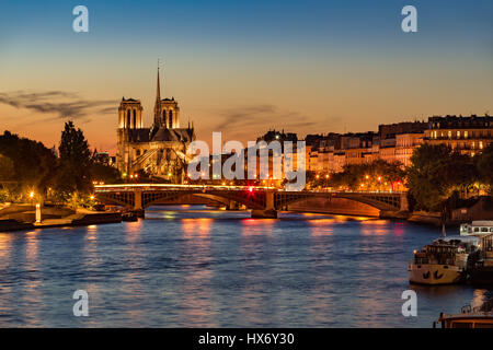 Notre Dame de Paris Cathedral, Seine River and the Ile Saint Louis at twilight. Summer evening with the Sully Bridge - Stock Photo
