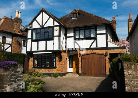 Mock Tudor black and white 1930's house with garage and a drive, in Esher, Surrey. UK. Photograph taken on a sunny - Stock Photo