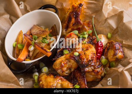 Spicy Chicken Wings with Hot Chili Jam, Baked Potatoes and Purple Carrots - Stock Photo