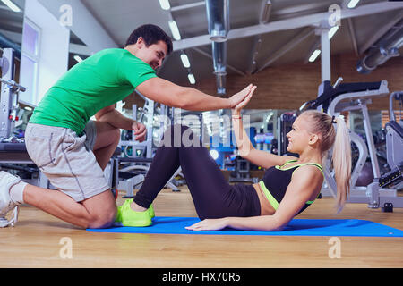 Sport girl doing abs exercises with a trainer man on the floor a - Stock Photo