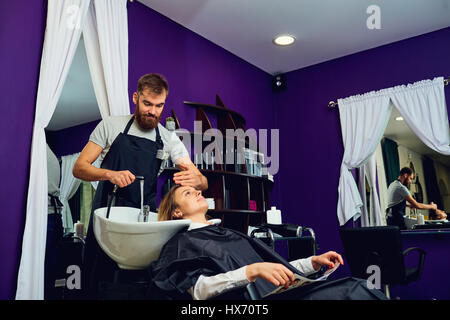 A hairdresser  man washes hair head to the client in the chair b - Stock Photo