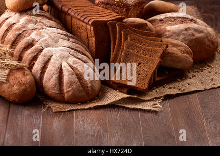 Freshly baked bread loaves on burlap on wooden table with wheat. Texture closeup bakery products - Stock Photo