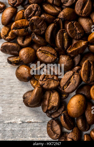 Roasted coffee beans on painted wooden board - Stock Photo