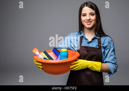 Young woman holding cleaning tools and products in bucket, isolated - Stock Photo