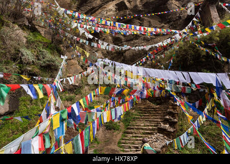 Prayer flags over the trail to the Tiger's Nest Monastery, or Taktsang Goemba, a Himalayan Bhuddist monastery perched - Stock Photo