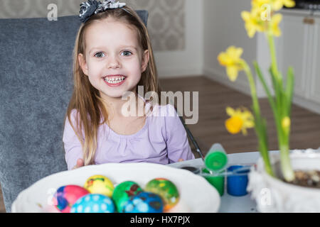 Smiling little girl coloring easter eggs. Cozy home atmosphere. Easter - Stock Photo