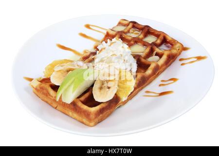 Dessert dish, Belgian waffle with condensed milk, whipped cream and slices of fruit, banana, apple, orange, put - Stock Photo