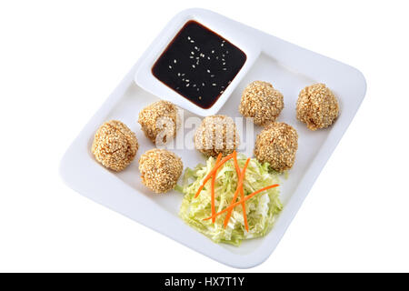 Asian cuisine, Chinese dishes, a set of balls sesame seeds chicken with a salad of fresh chopped cabbage and a cup - Stock Photo